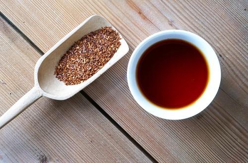 getrockneter Rooibos neben einer Tasse Rooibos Tee